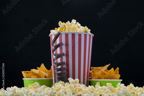 Foto op Canvas Buffet, Bar cinema snack, popcorn and two buckets of nachos on a black background