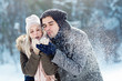 Leinwandbild Motiv Two young people enjoying in the snow