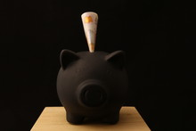 Saving Money - Black Piggy Banks With 10 Pounds On Black Background With Lightings