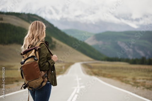 Fototapeta A woman with a backpack and a road stretching into the distance against the backdrop of mountains obraz
