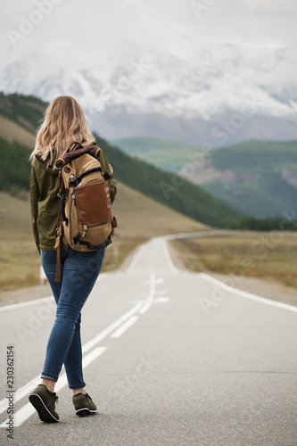 Obraz A woman with a backpack and a road stretching into the distance against the backdrop of mountains - fototapety do salonu