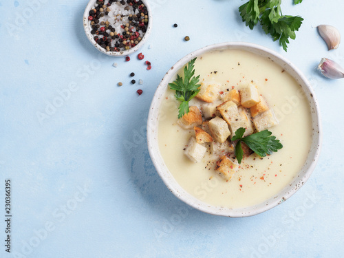 cauliflower potato soup puree on blue tabletop, Creamy cauliflower soup with toasted bread croutons. Vegetarian healthy food concept. Ideas and recipes for winter meal. Top view or flat lay.Copy space