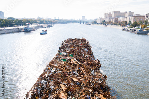 barge with trash floats down the river Fototapeta