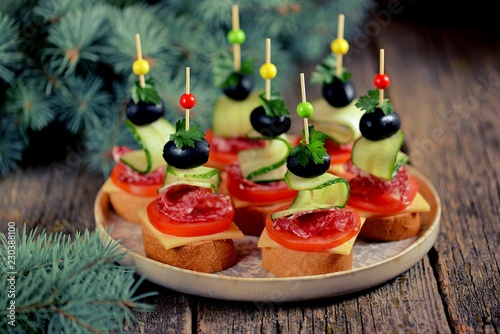 Canapé on skewer from bread baguette with toast cheese, sausage, tomato, cucumber and olives. Traditional snack for the New Year.