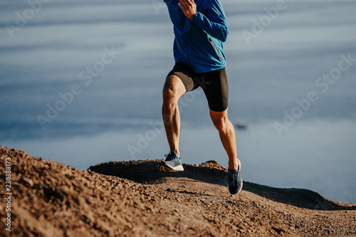 Photo man runner run steep mountain on background of sea