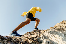 Male Athlete Climbs Up A Steep Mountain. Concept To Overcome Difficulties