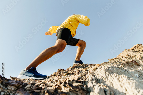 Fotomural male athlete climbs up a steep mountain