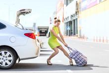 Stylish Woman Houls Heavy Big Bag To Car Trunk In Summer Day.