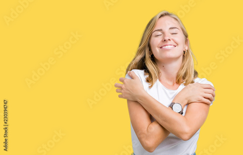 Photo Beautiful young woman wearing casual white t-shirt over isolated background Hugging oneself happy and positive, smiling confident