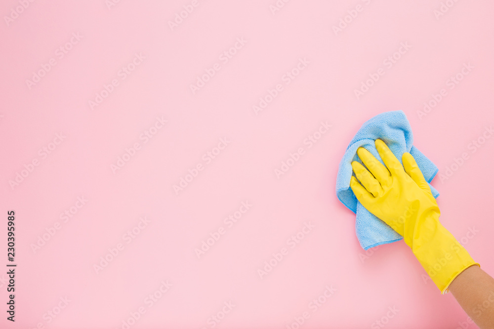 Valokuva Employee hand in yellow rubber protective glove wiping pastel pink wall from dust with blue dry rag