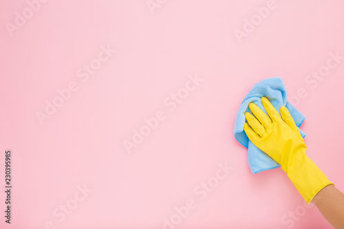 Valokuvatapetti Employee hand in yellow rubber protective glove wiping pastel pink wall from dust with blue dry rag