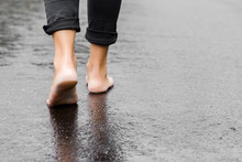 Young Woman's Barefoot Walking On The Wet, Dark Black Asphalt After Warm Rain. Cloudy Day In Summer. Back View. Empty Place For Text.