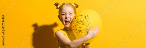 Photo  Girl with red hair on a yellow background