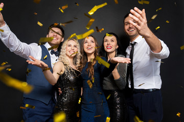 Fototapeta celebration, people and holidays concept - happy friends at party under golden confetti over black background
