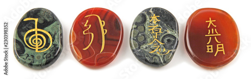 Photo  The four major Reiki Healing Symbols - etched into palm stones made of Carnelian