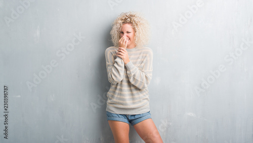 Fotografie, Tablou  Young blonde woman with curly hair over grunge grey background smelling something stinky and disgusting, intolerable smell, holding breath with fingers on nose