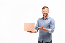 Casual Young Man Holding A Box Isolated On A White Background