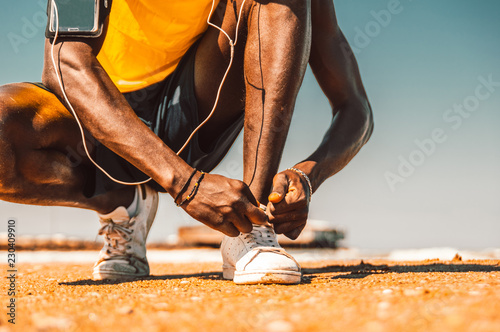 Fototapeta Close up of a black man hands tying shoelaces before training starts