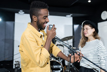 Side View Portrait Of Contemporary Music Band Rehearsing, Focus On Smiling African-American Man Singing To Microphone, Copy Space