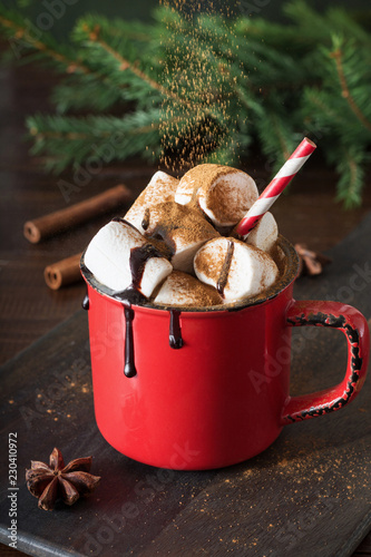 Mug of hot chocolate and cacao with marshmallows with christmas tree branches on wooden board. Xmas holiday.