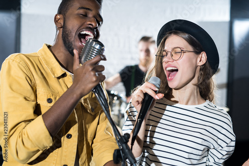 Fotografia  Waist up portrait of two young people enjoying singing with microphones during b
