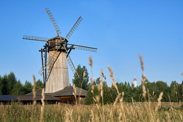 Fototapeta Wooden windmill with ears of wheat growing in the field on the foreground