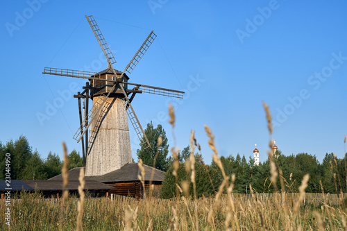 Wooden windmill with ears of wheat growing in the field on the foreground
