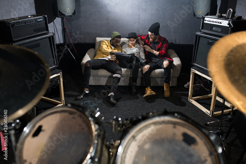 Fotografía  Full length portrait of three contemporary young people sitting on couch and chi
