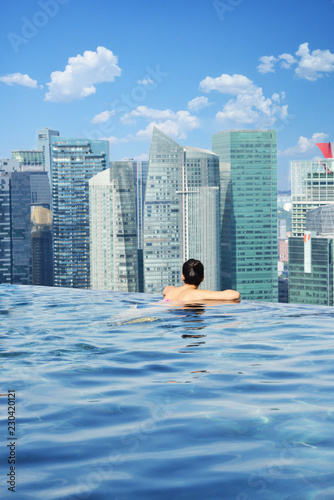 Attractive woman relaxing and enjoying the view in Marina Bay sands infinity pool, Singapore, October 16, 2018
