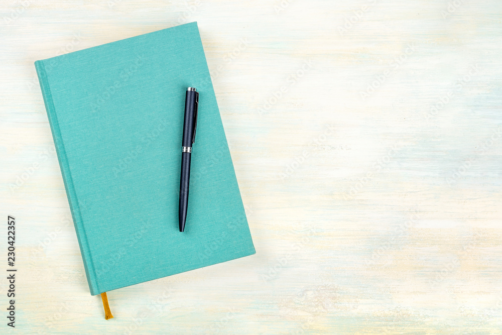 Fototapeta A photo of a teal blue journal with a pen, an elegant diary, notebook or planner, shot from above with copy space