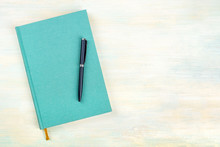 A Photo Of A Teal Blue Journal With A Pen, An Elegant Diary, Notebook Or Planner, Shot From Above With Copy Space