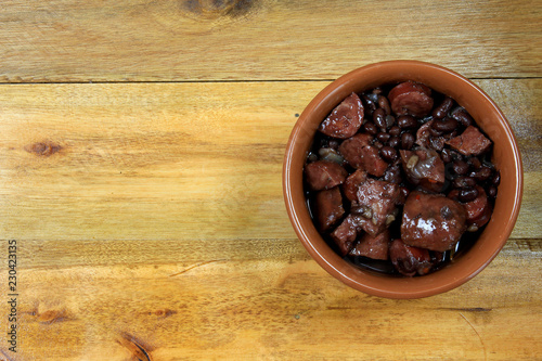 Foto  pot with feijoada, traditional brazilian cuisine dish, isolated under wooden bac