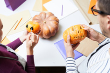 Close-up Of Busy Colleagues Standing At Table And Making Design For Halloween Pumpkins, Man Carving Pumpkin While Woman Painting Small Pumpkin In Studio