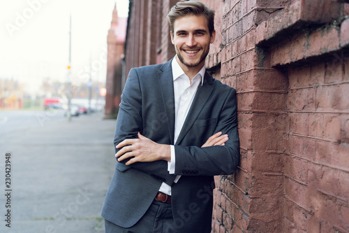 Fototapeta Smiling young male manager formal dressed leaning on a wall outdoors. obraz