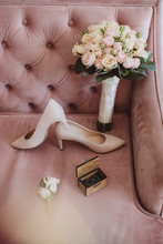 Bridal Bouquet With Wedding Shoes And Wedding Rings On A Vintage Sofa