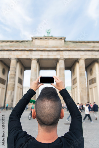 Photo  young man taking a picture of the Brandenburg Gate