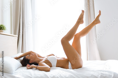 Fotografie, Obraz  Beautiful smiling young woman with fresh skin in underwear having fun lying on bed at home