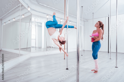 Fototapeta Watching professional. Dark-haired student of pole dance studio watching professional dancer moving obraz