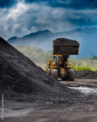 Fotografie, Obraz Coal: loader moving a pile of coal at a coal mine on Vancouver Island