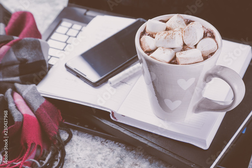 Winter cozy workspace with computer, phone, notepad, cocoa copy space