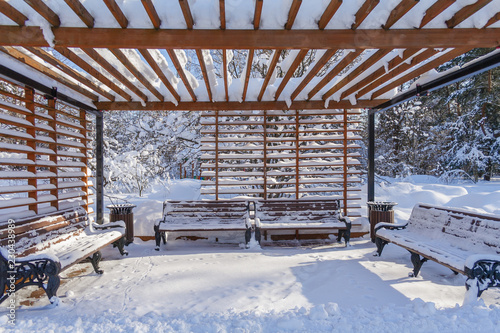 Leinwand Poster Benches under a wooden arbour in the winter forest