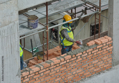 Fototapety, obrazy: Bricklayer lay clay bricks to form building walls at the construction site.