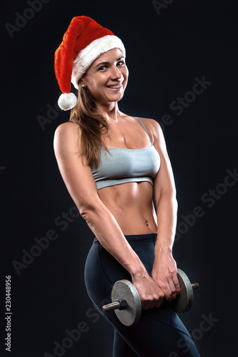 Fotografia  Attractive fitness woman is standing with dumbbells in christmas hat
