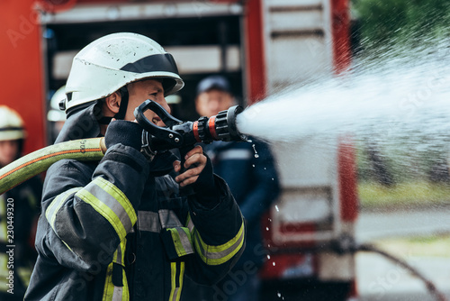 Photographie selective focus of firefighter with water hose extinguishing fire on street