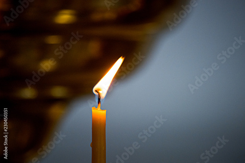 Fotografiet  Burning church candle is close