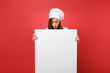 canvas print picture - Housewife female chef cook baker in striped apron, white t-shirt, toque chefs hat isolated on red background. Woman hold big white blank billboard for promotional content. Mock up copy space concept.
