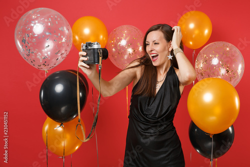 Photo  Stunning girl in black dress doing taking selfie shot on retro vintage photo camera, putting hand on head on bright red background air balloons