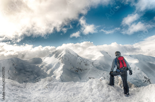 Photo skier stay with skis on big rock on mountains backdrop