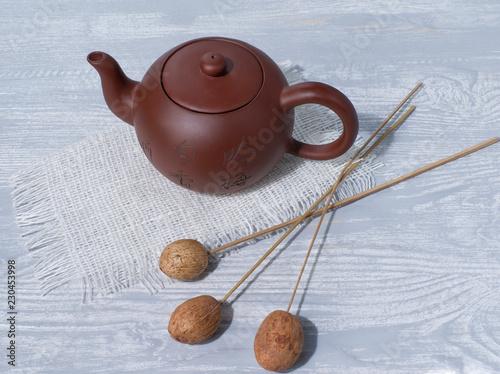 Fotografía  teapot, napkin and wooden bouquet, on wooden background, still life for restaura