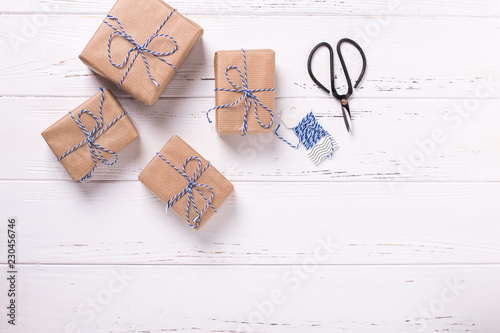 Wrapped gift boxes with presents on textured wooden background.